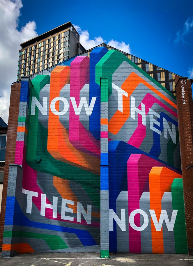 "A colourful graffiti'd wall that says ""THEN"" and ""NOW"" in large block letters"