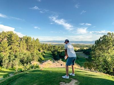 man playing golf during daytime golf teams background