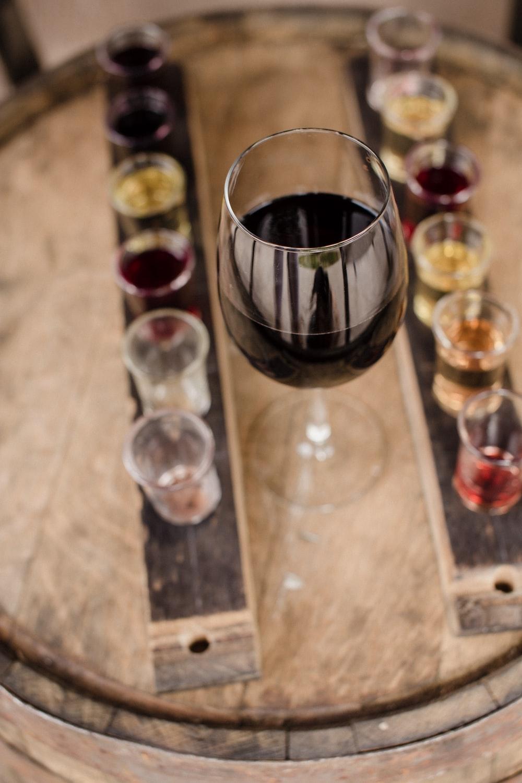 red wine on glass near shot glasses