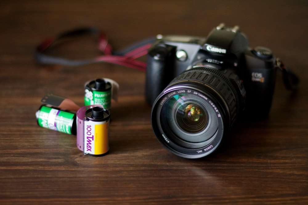 Canon EOS DSLR camera beside three roll films on brown panel