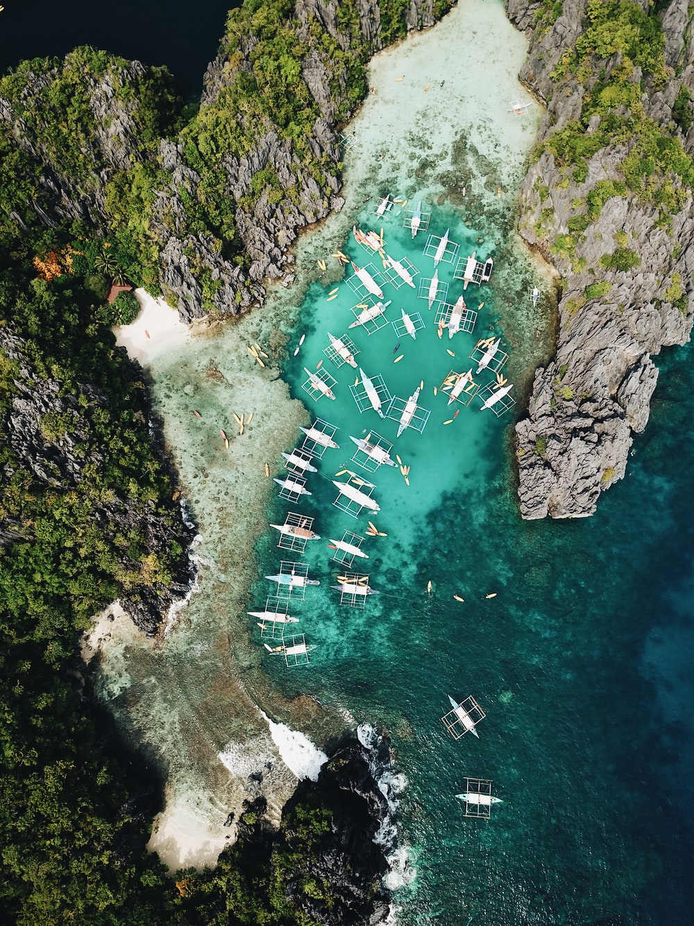 aerial photography of boats beside mountain during daytime