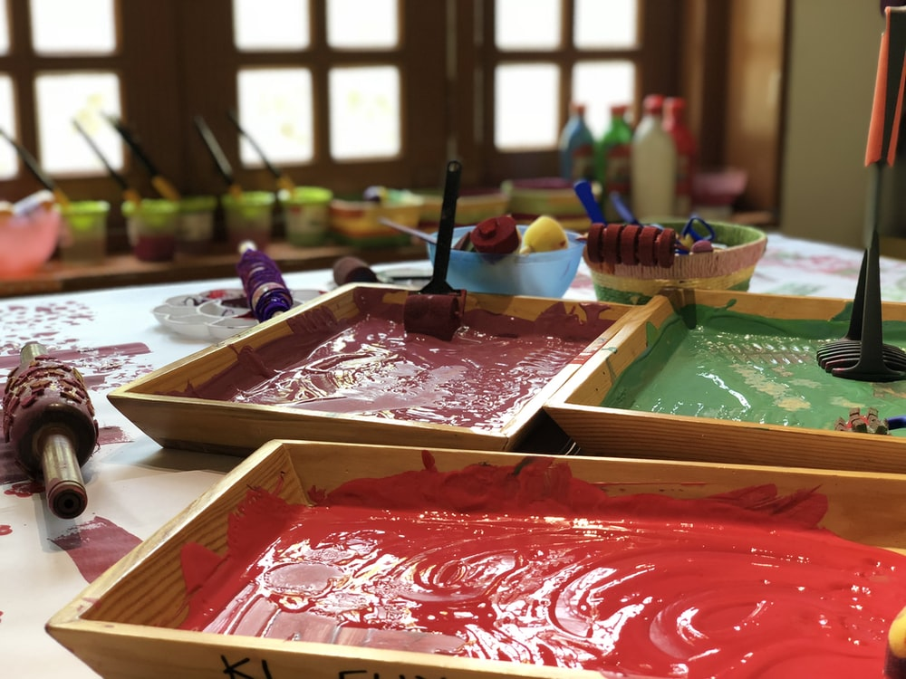 assorted paints in brown wooden trays on table