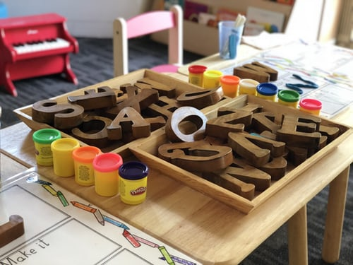 Wooden alphabet letters and play-dough on a table in a classroom