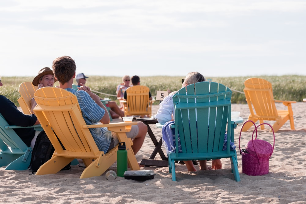 people sitting on outdoor chairs on shore
