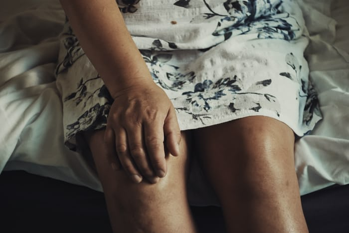 A woman sitting with her hand on her right knee as if in pain