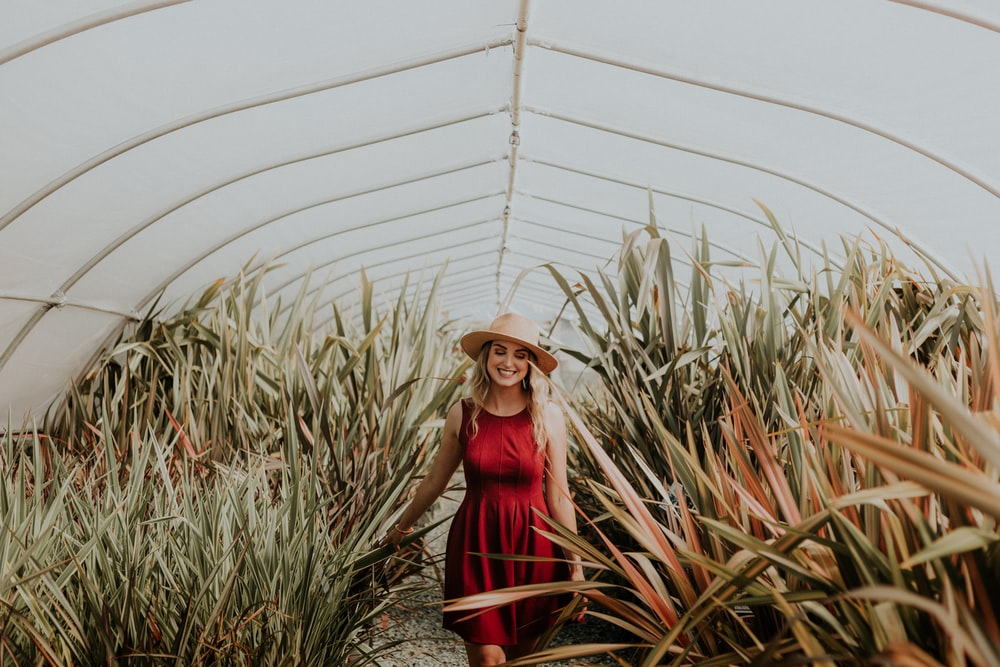 smiling woman inside green house
