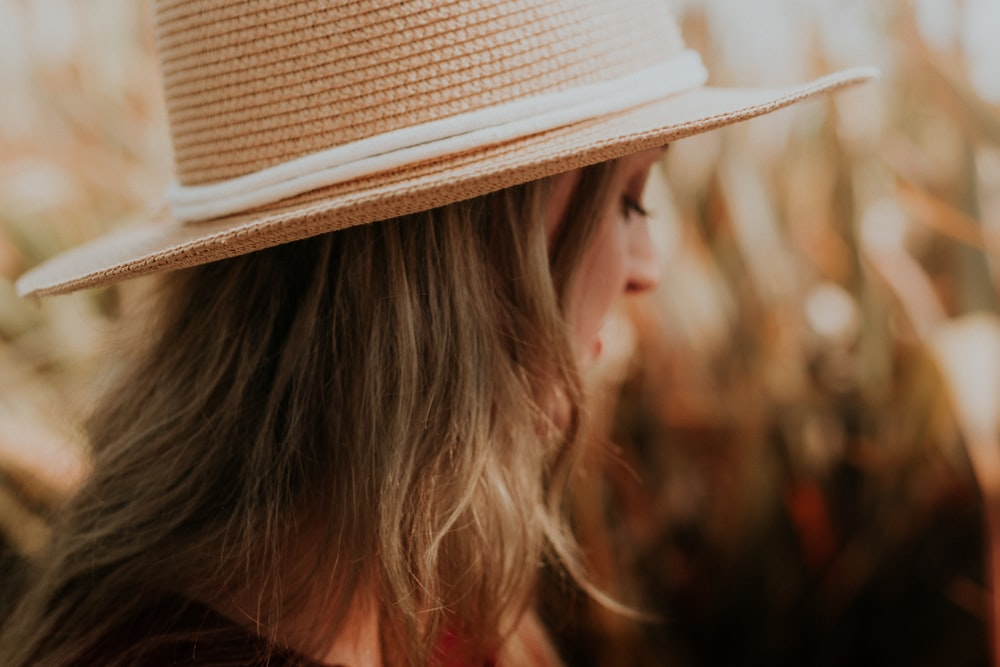 selective focus photography of woman wearing straw hat