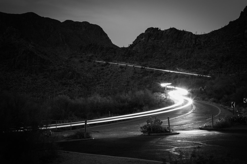 grayscale photography of road beside mountain