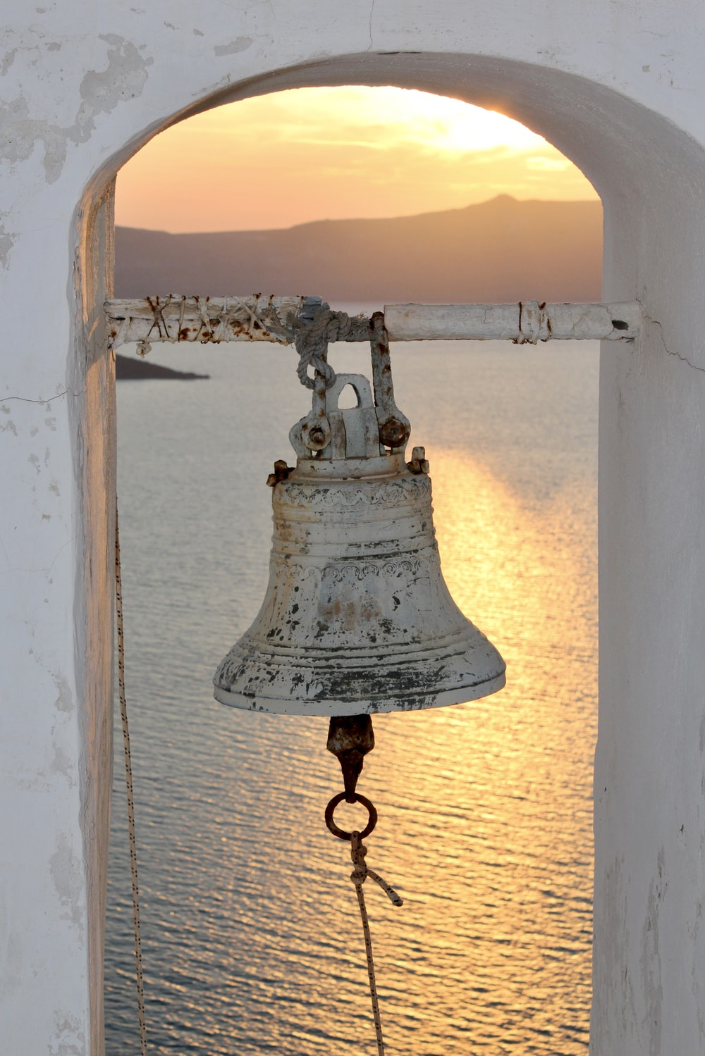 white and black metal bell near body of water