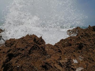 water splashing on brown rock