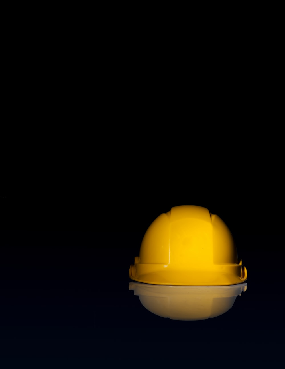 yellow safety hat on black surface