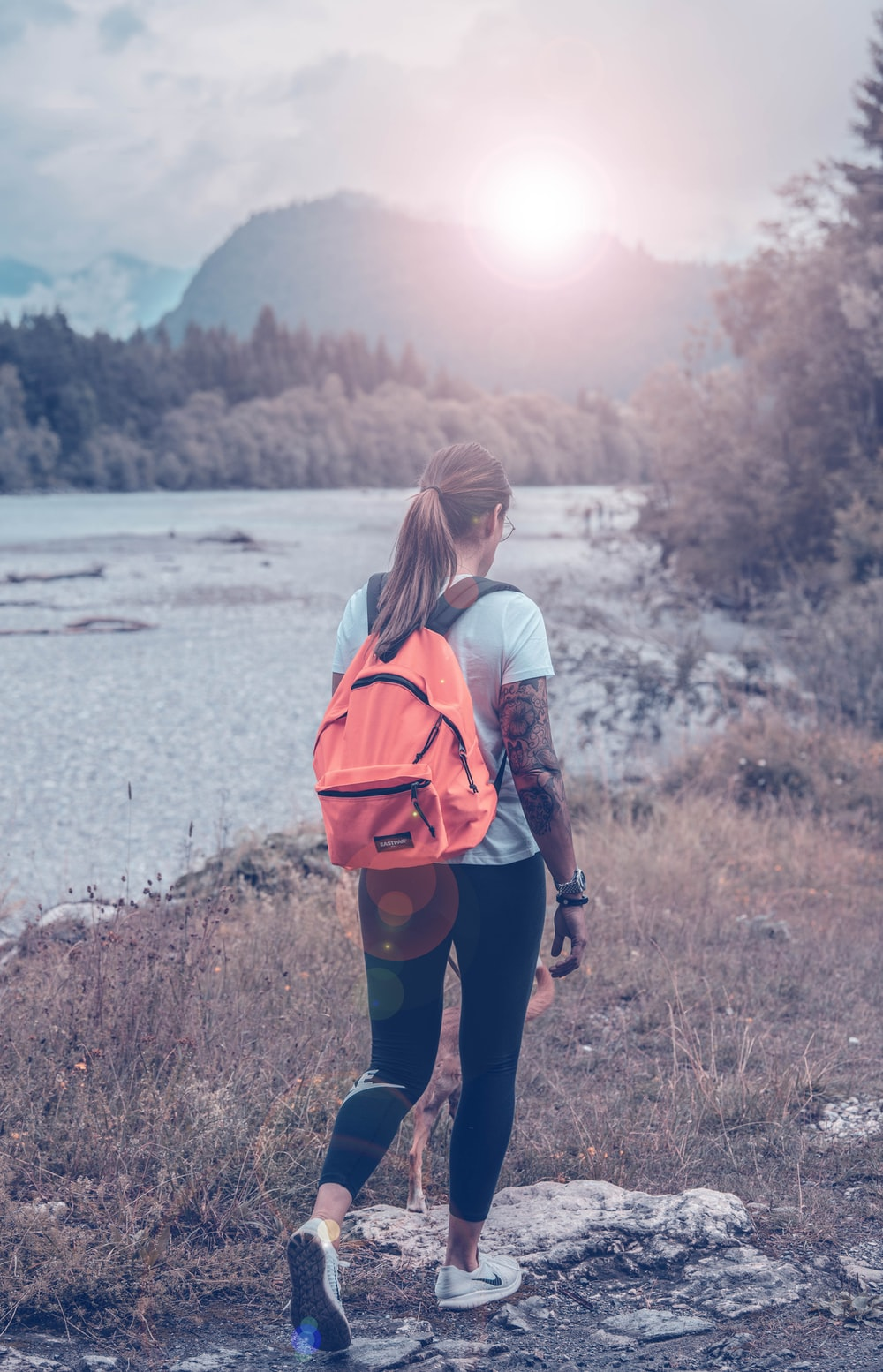 woman carrying orange leather backpack standing near body of water