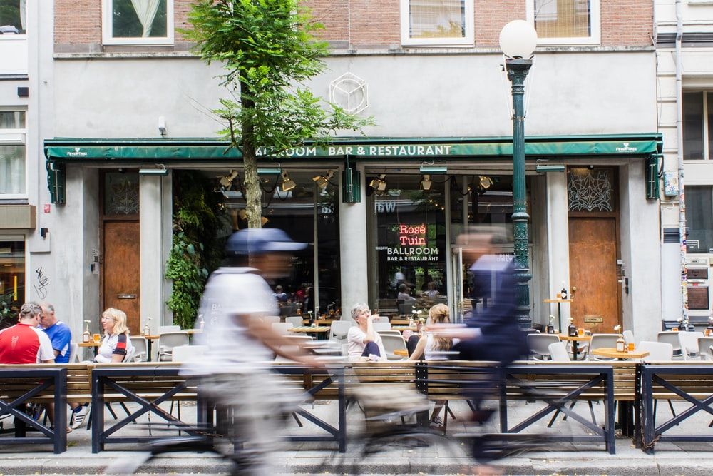 timelapse photo of person riding bike passing by storefront during daytime