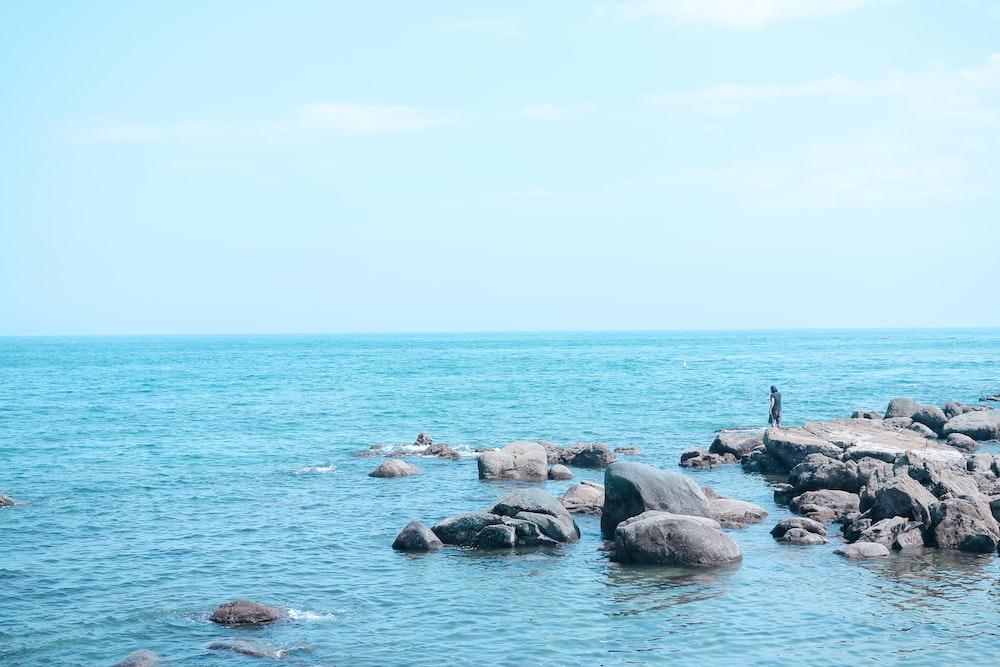 man standing on rock near beach