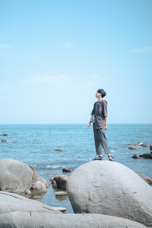 man standing on rock on seashore