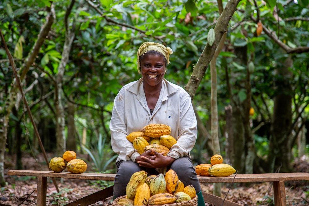 women holding cacao fruit close-up photography