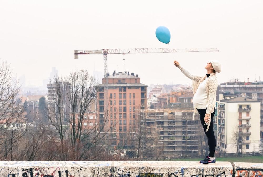 woman on roof holding balloon