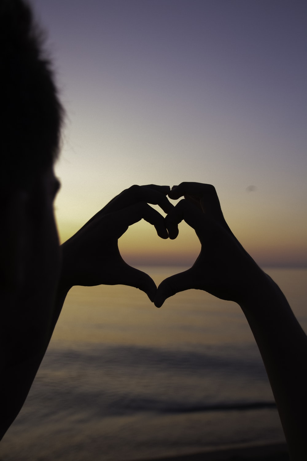 silhouette of person doing heart handsign