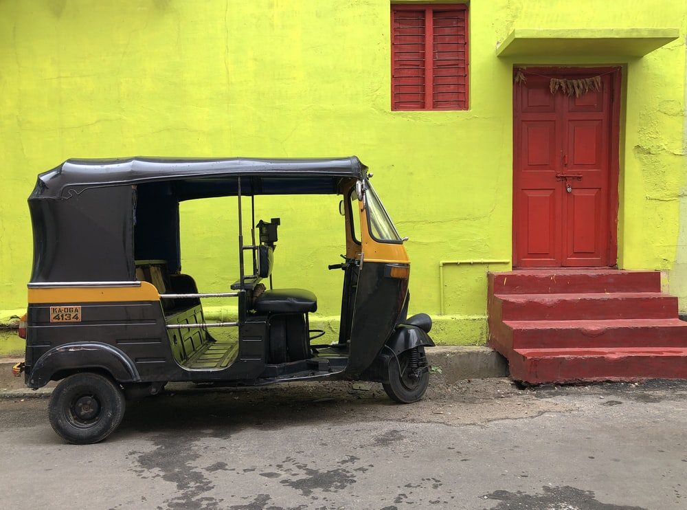 black and yellow vehicle near yellow wall and red door close-up photography