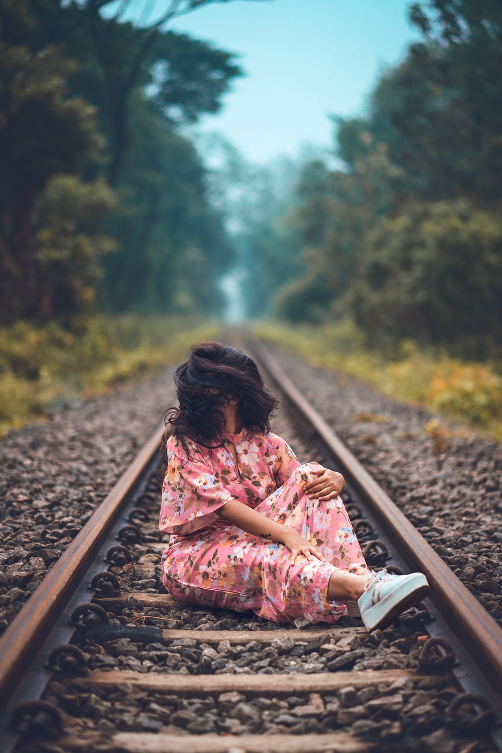 woman in pink floral short-sleeved dress sitting on train railing