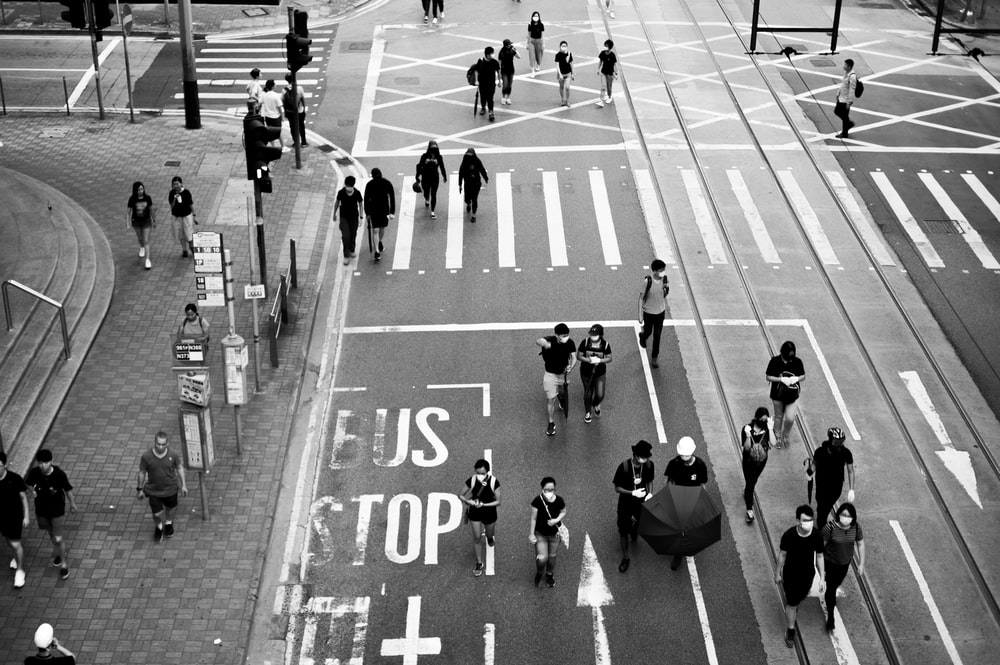 grayscale photo of people crossing road