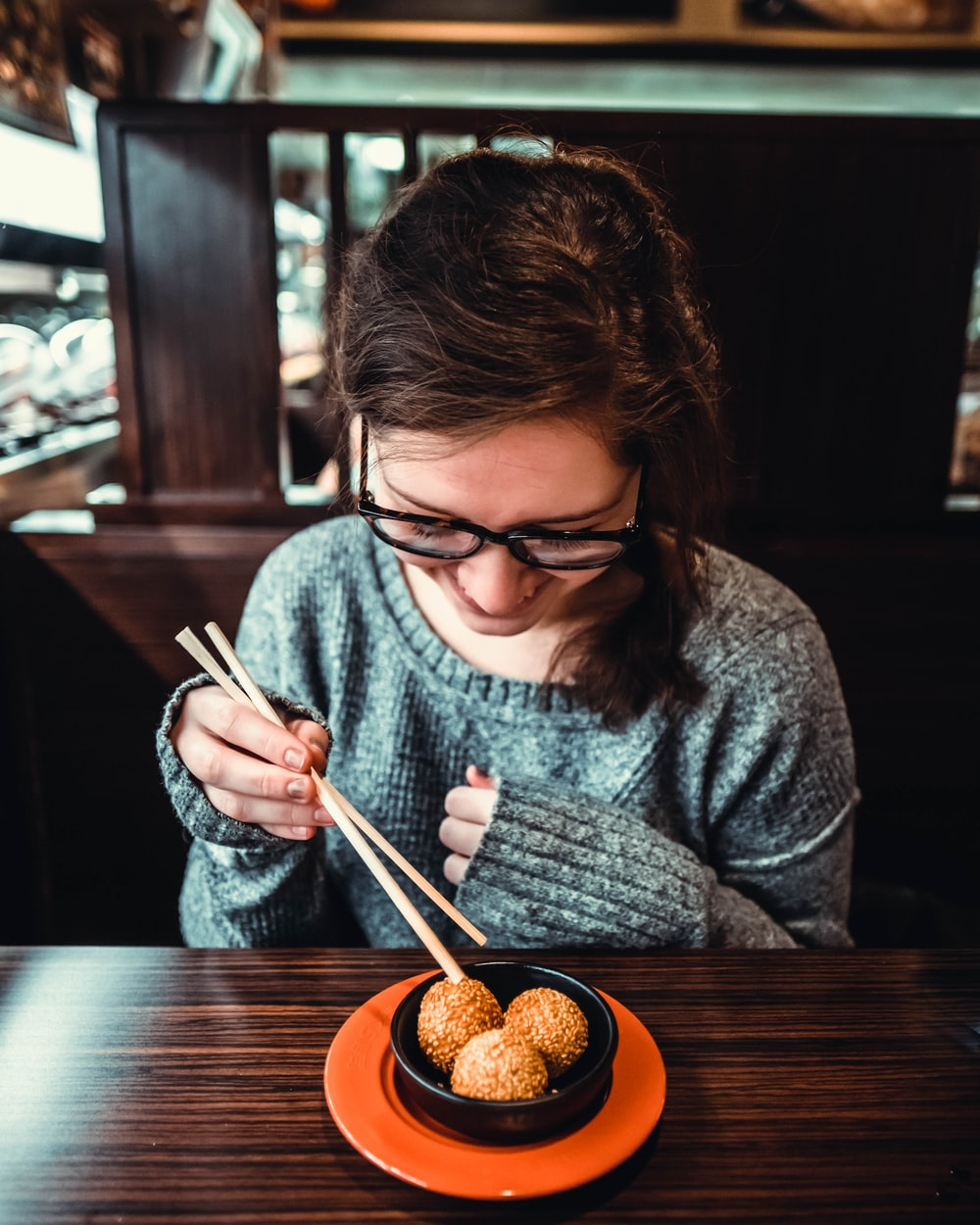 woman smiling while picking up food using chopstick