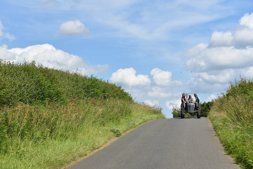 people riding on tractor at the hill