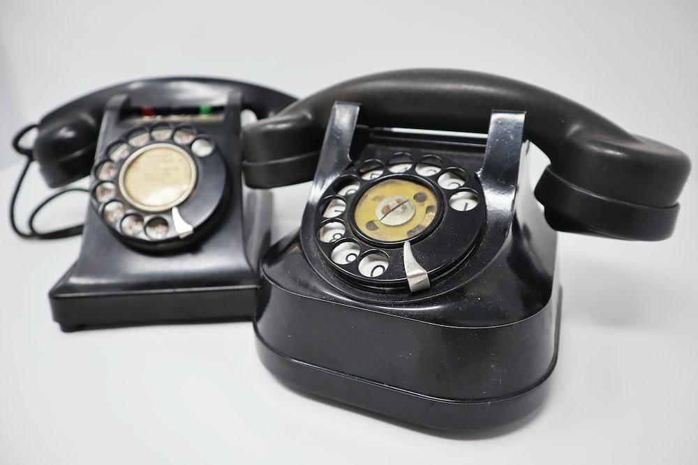 two black rotary telephones