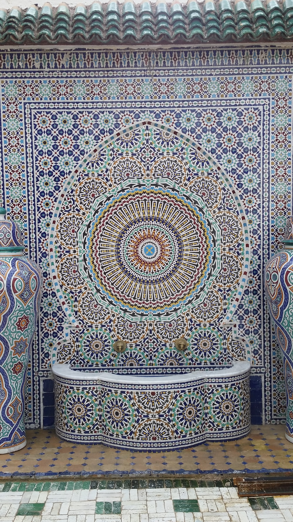 white, blue, and brown floral tiled fountain outside of building