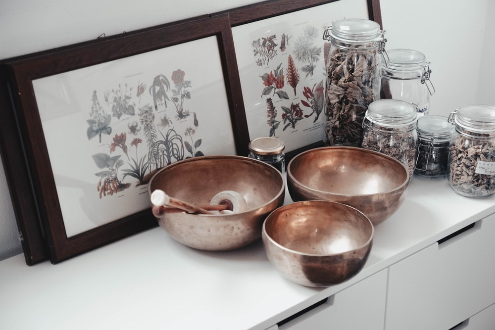 stainless steel bowls on table near framed photos