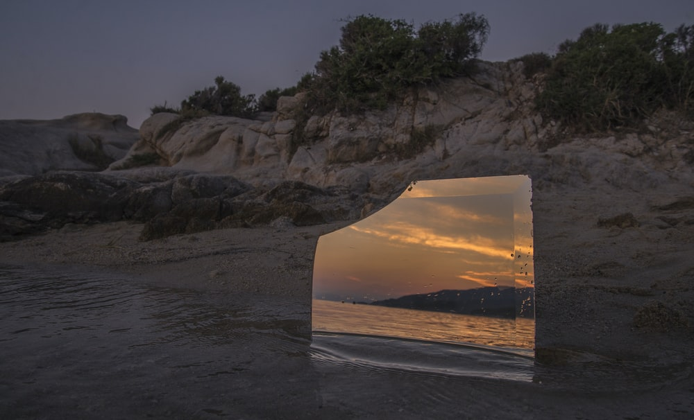 glass mirror on shore during golden hour