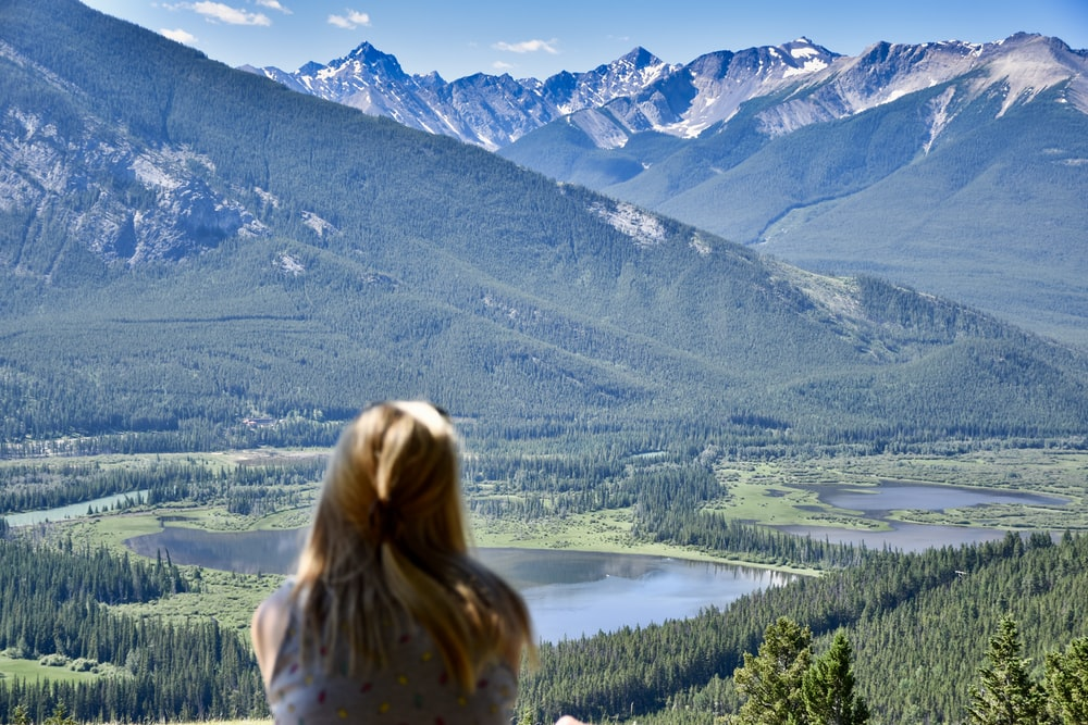 woman looking on green and white mountain view