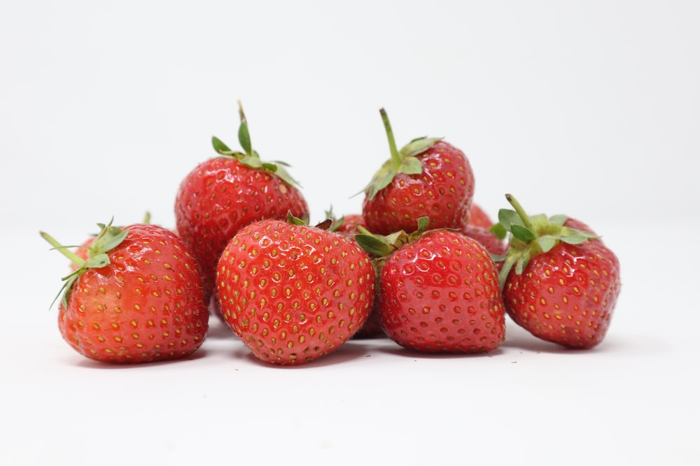 bunch of strawberries in white surface