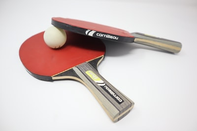 two red pingpong rackets on white surface table tennis zoom background