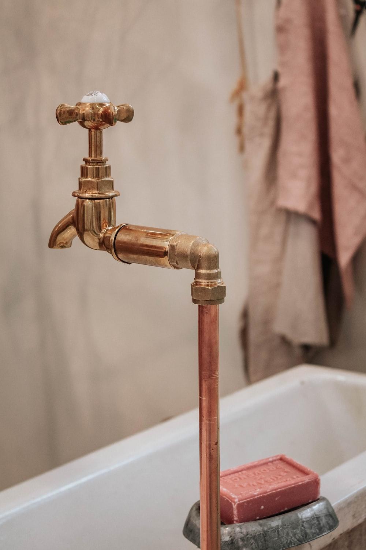 brass faucet near bathtub