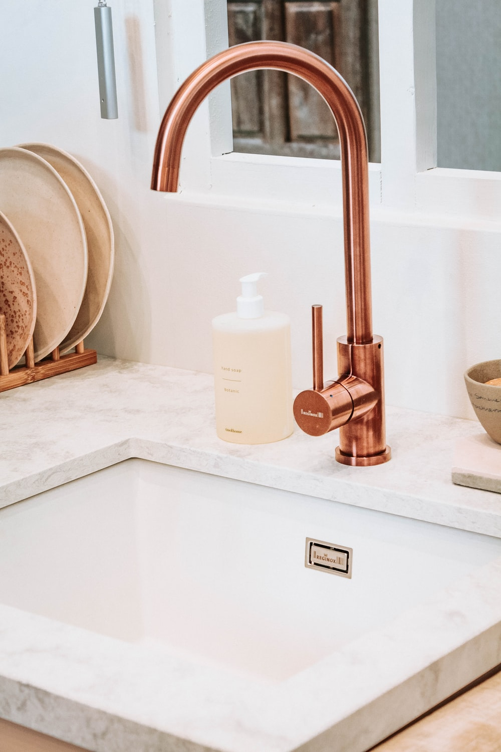 square white sink with brass faucet