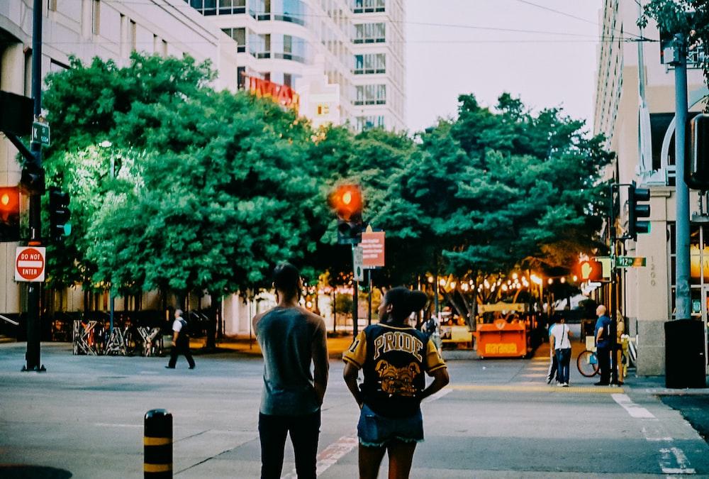 two men standing on sidewalk during daytime