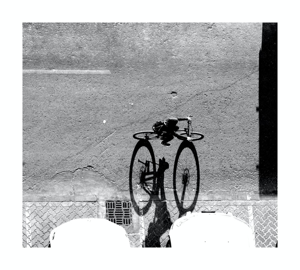 grayscale photography of person riding on bike