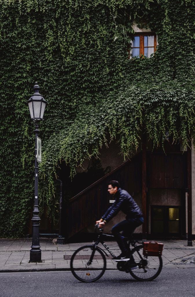 men driving bike near house and street lamp during daytime
