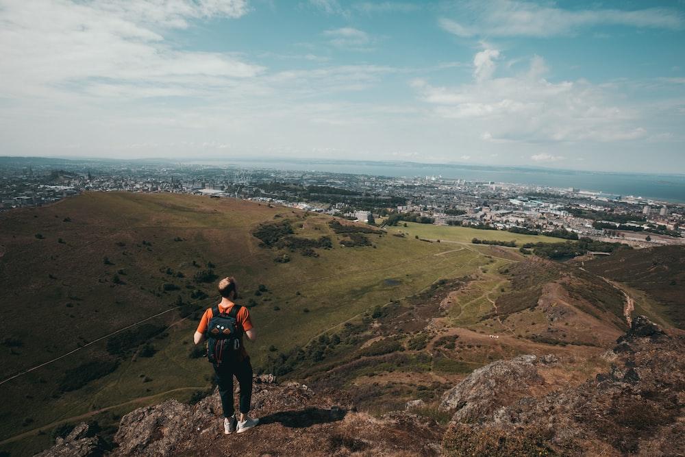 person wearing orange shirt standing across horizon