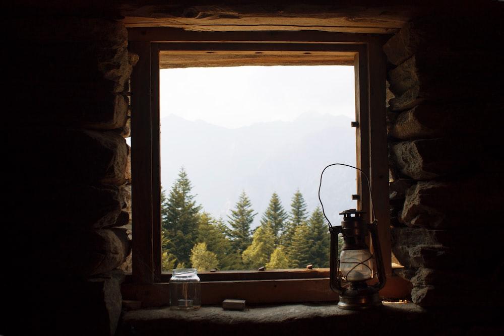 black lantern lamp near open window viewing green trees