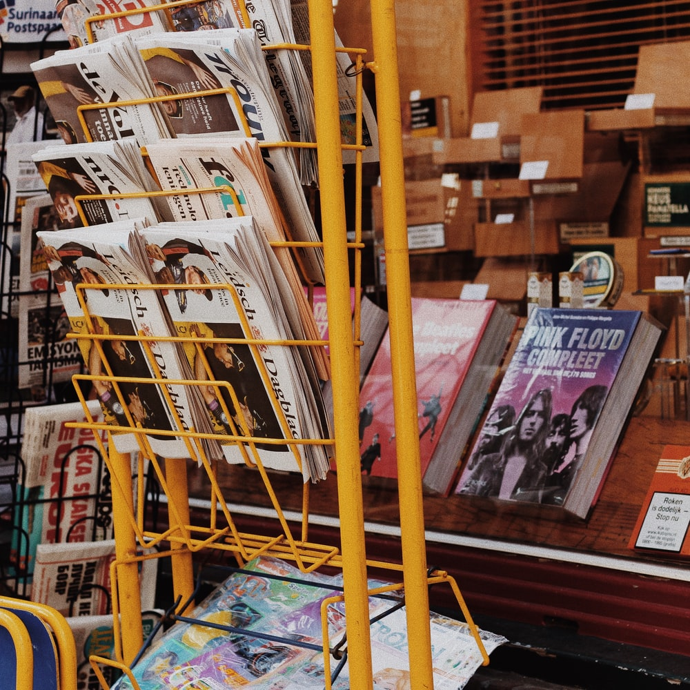 assorted magazines and newspapers lot on yellow metal rack