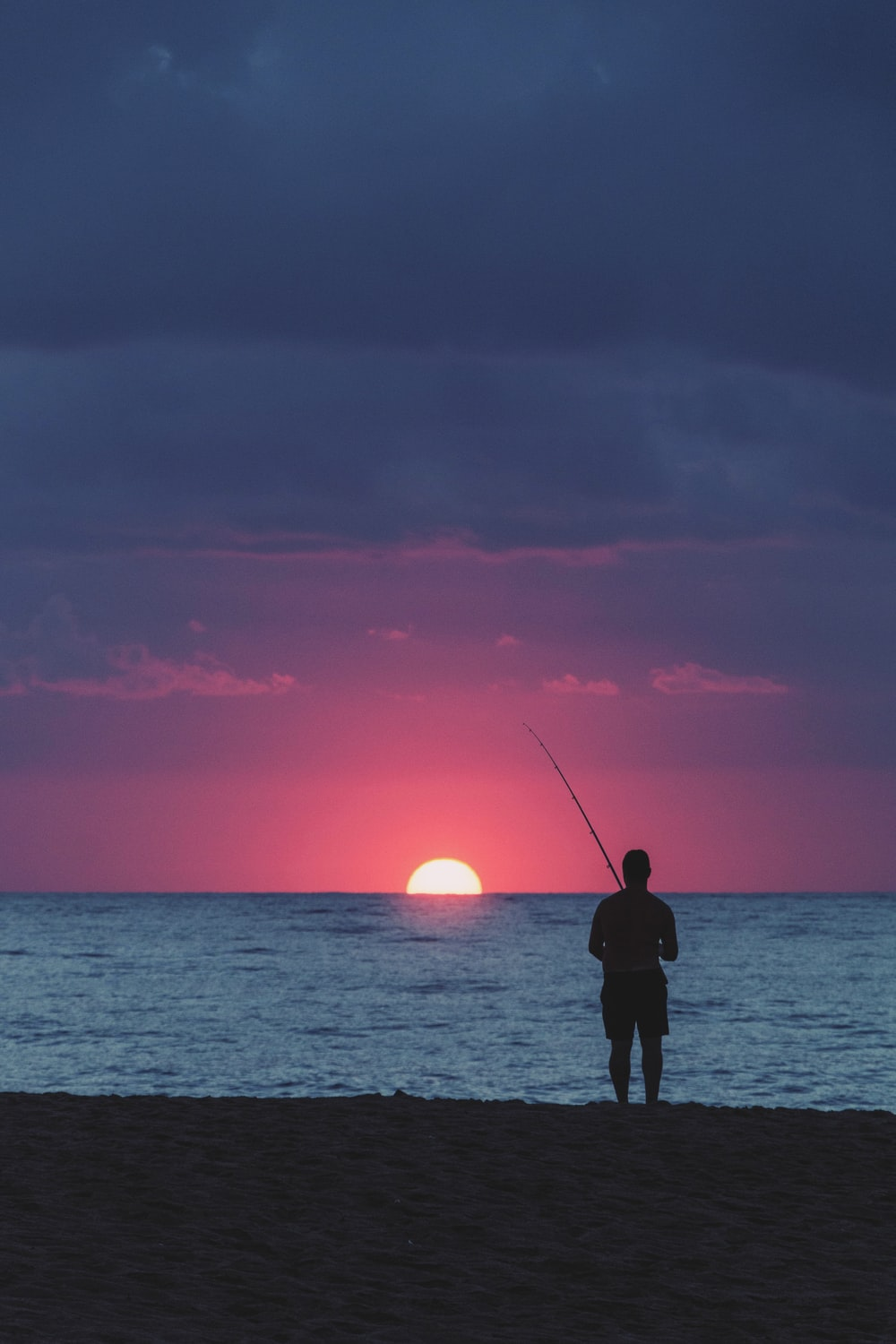 silhouette photography of man fishing in the sea during golden hour