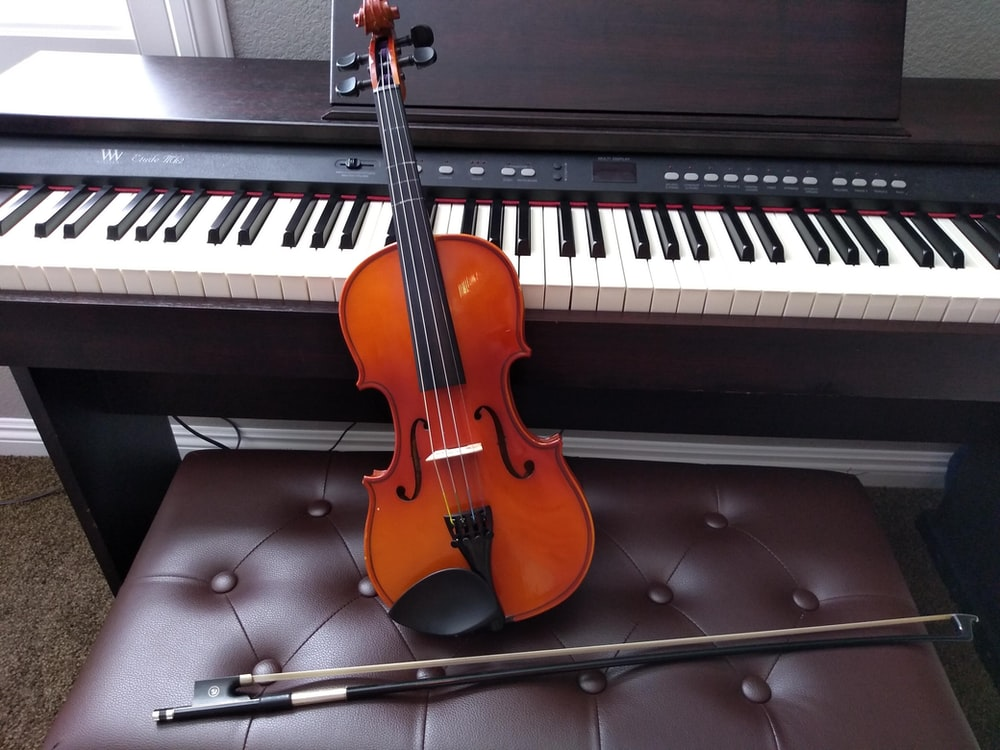 brown violin with brown violin bow beside white electronic keyboard