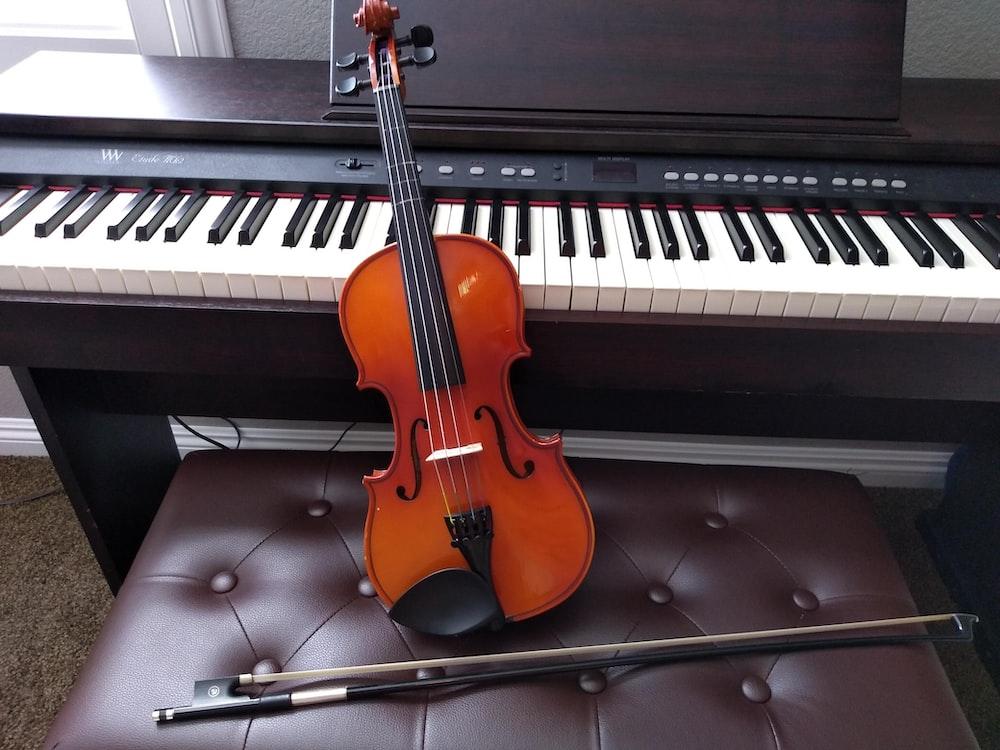 茶色のバイオリンと白い電子キーボードの横にある茶色のバイオリンの弓