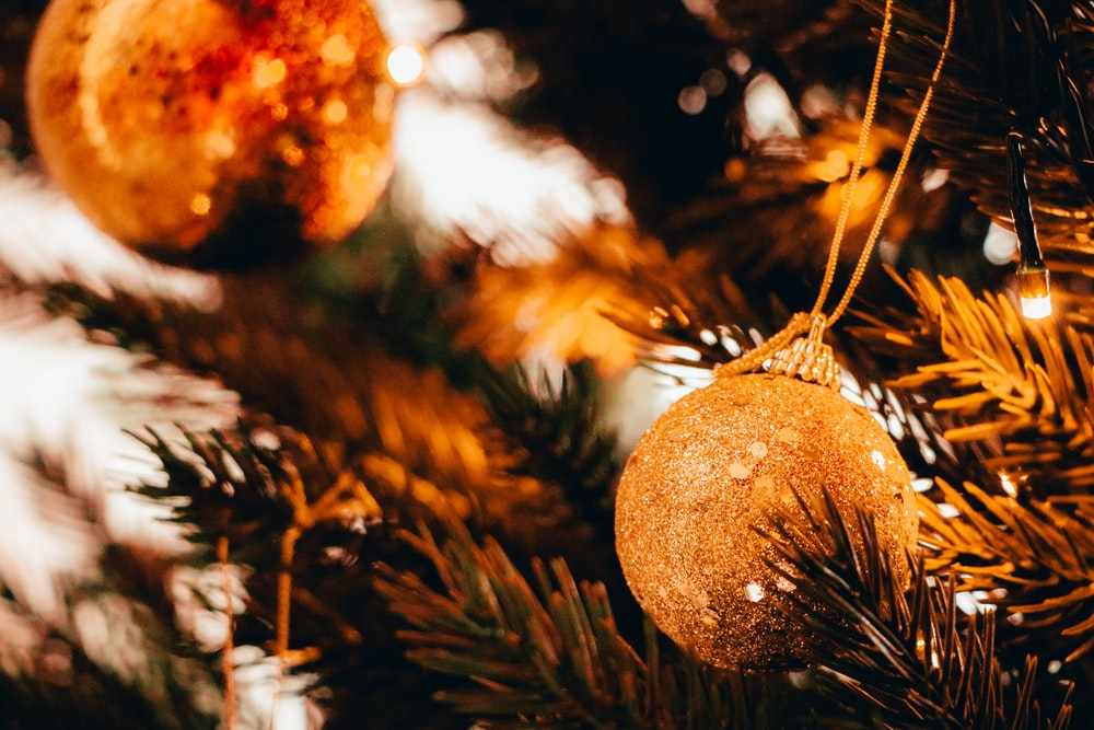 bokeh photography of gold Christmas bauble hanging from a tree