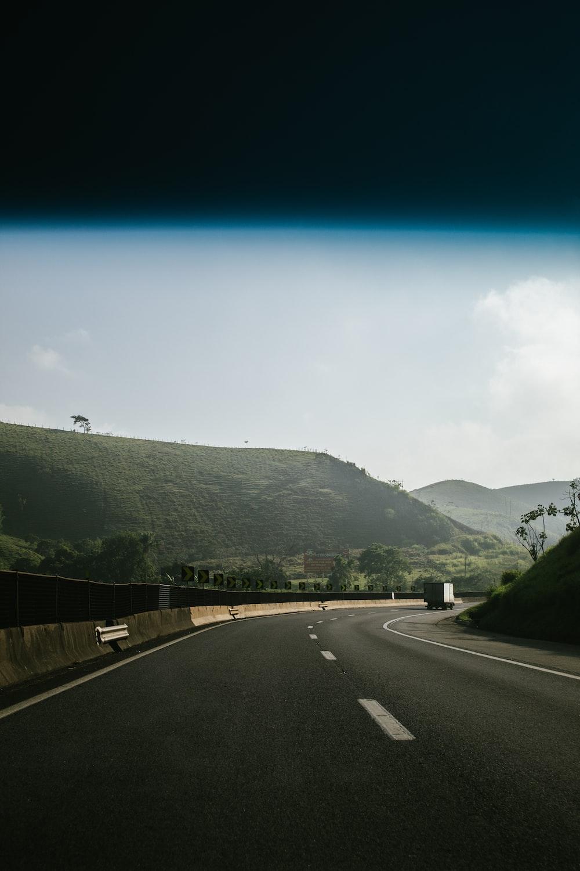 black asphalt road between green mountains