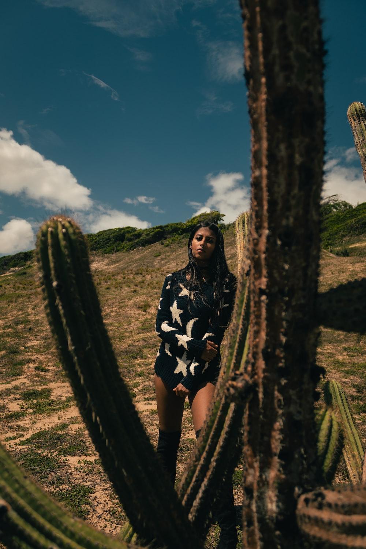 woman standing beside cactus