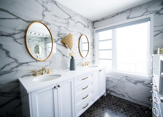 Bright marble and gold bathroom with two sinks and two mirrors.