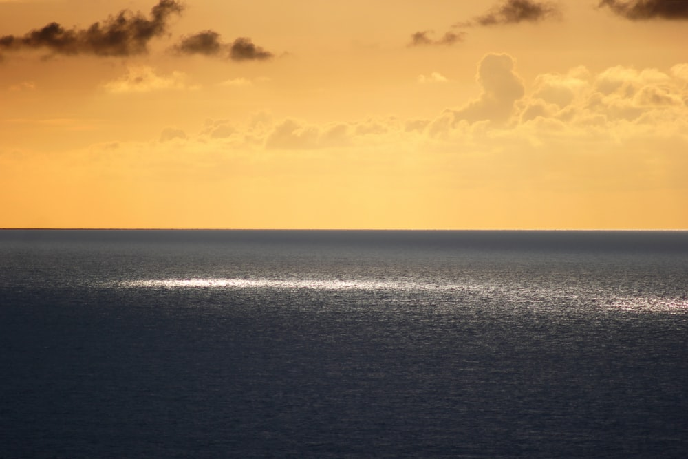 gray sea under orange skies
